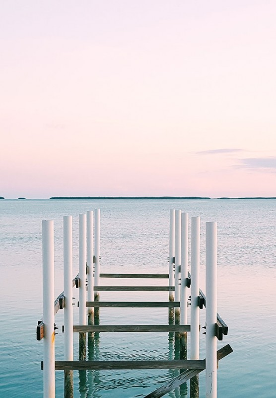 A dock going out over water during a sunset