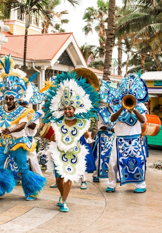 A Junkanoo band in colorful blue costumes plays instruments and dances outdoors in Nassau.