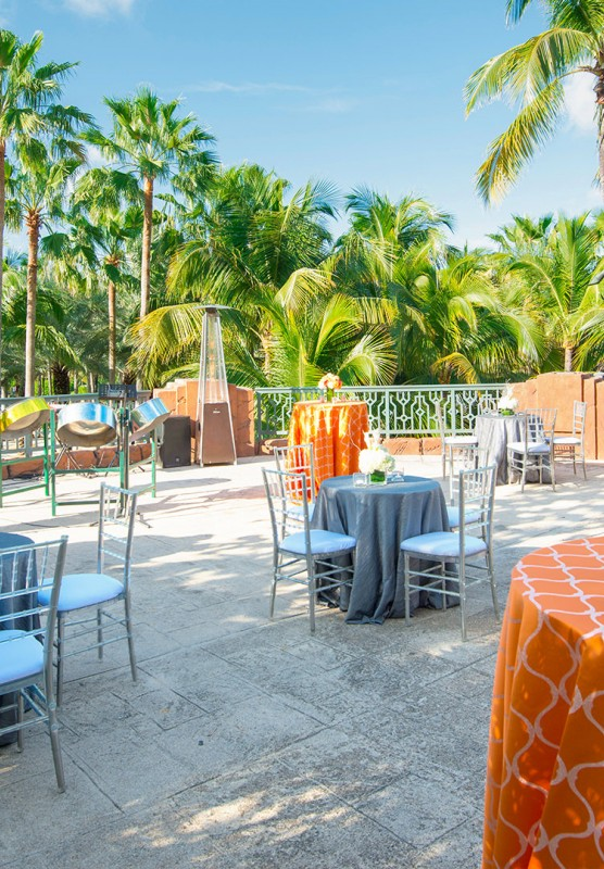 A patio set up for guests on a blue sky day, surrounded by palm trees.