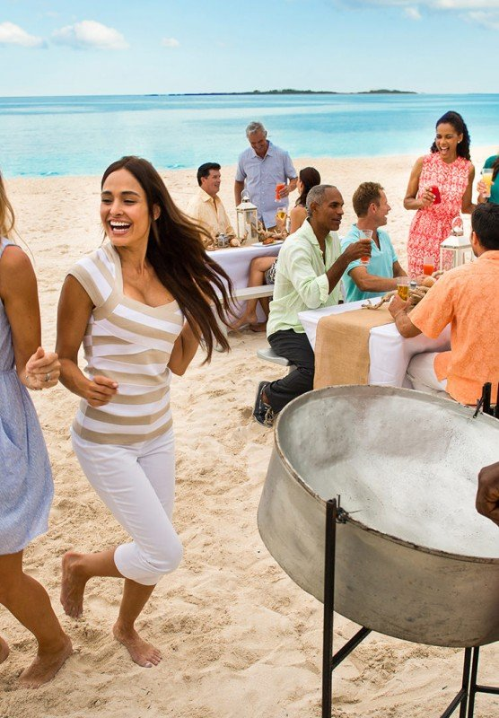 Two women dancing on a sandy beach together while a man plays steel drums. A group of people sit at picnic tables behind them.