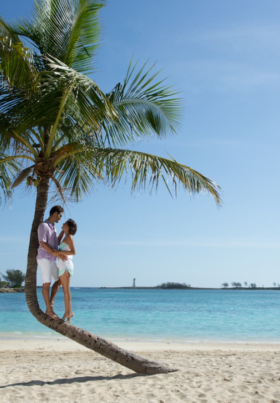 A couple relaxes under the shade of a palm tree on a Bahamas beach