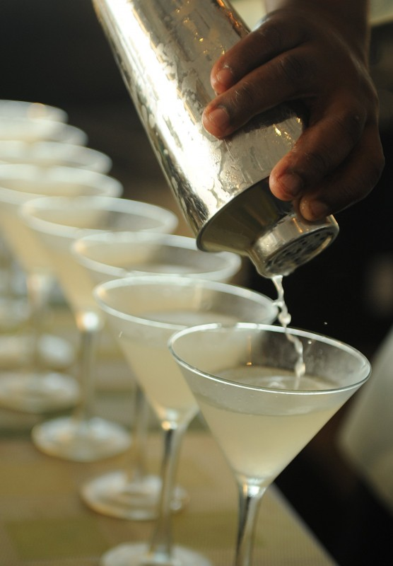 A freshly made cocktail is poured from a cocktail shaker into a row of martini glasses.