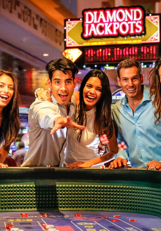 A group of men and women enjoying a game of craps in a casino.
