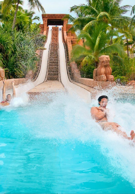 Two people splashing into a pool after sliding down the Challenger Slide at Aquaventure.