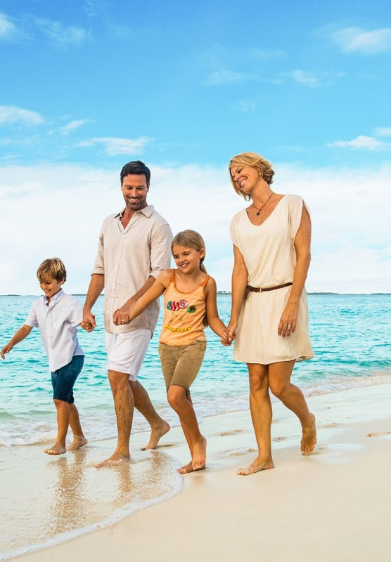 A family of four walking hand-in-hand down a tropical white sand beach.