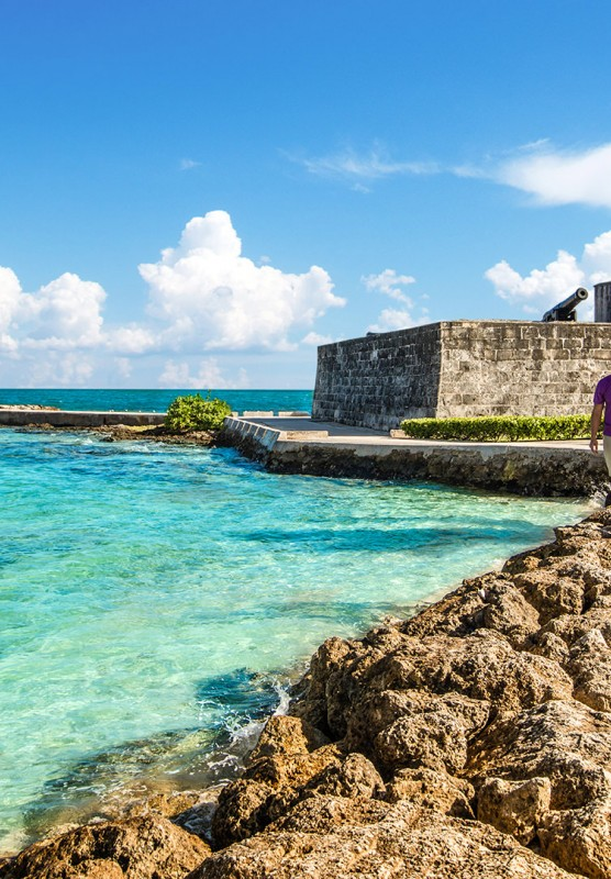 A couple walking hand-in-hand along the rocks at Fort Montague, Bahamas.
