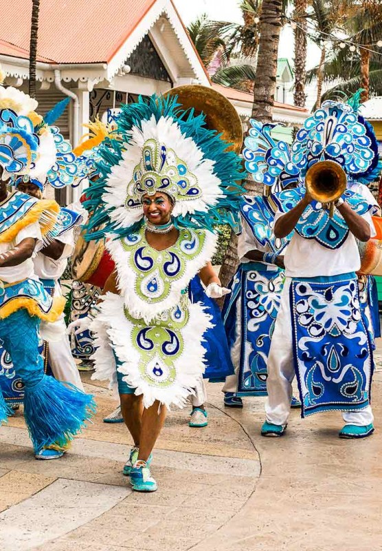 People dressed in intricate costumes walk down a sunny street.