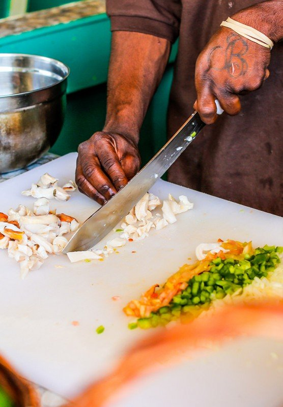 A man slices vegetables on a white cutting board.