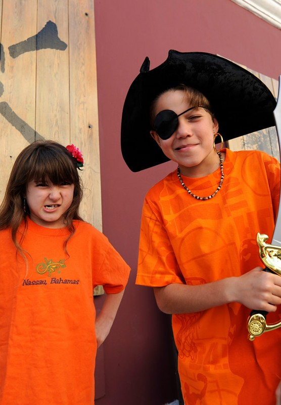 A young girl and a young boy wearing pirate swag outside of the Pirate Museum.