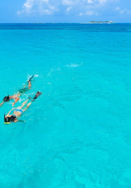Man and woman swimming in blue water