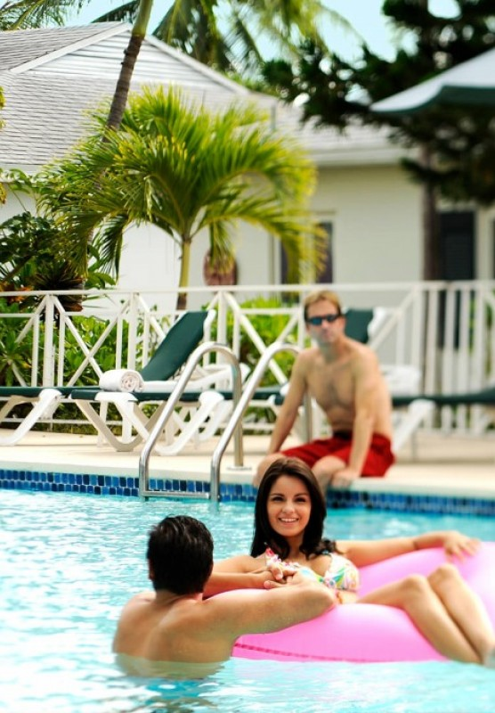 Groups of young people relax in and around a resort pool.