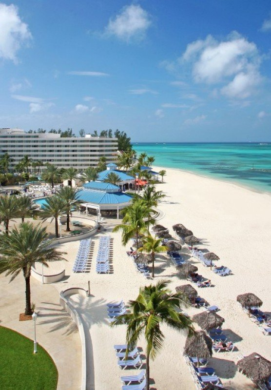 The sandy beach at Melia Nassau surrounded by blue waters and palm trees in the background