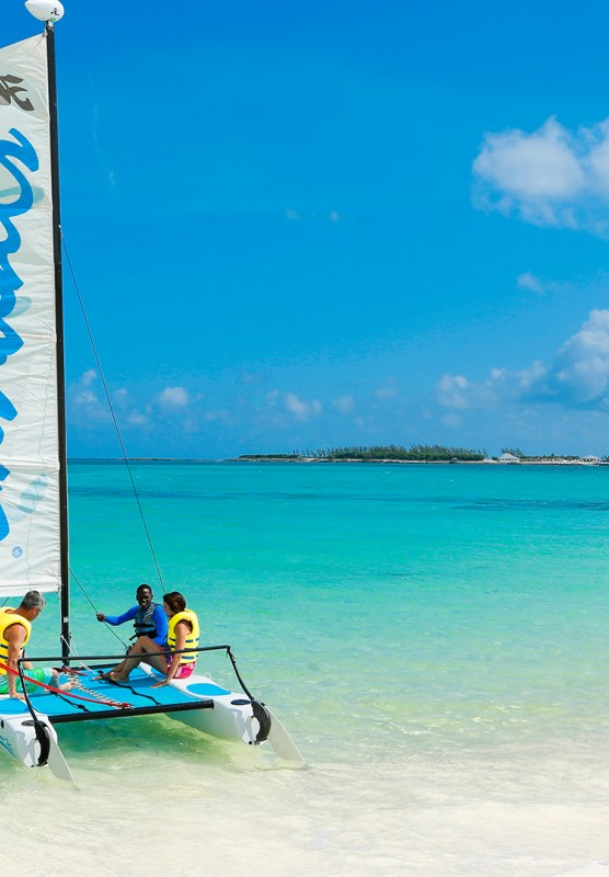 A Sandals branded catamaran floating in clear ocean water, while two guests with yellow lifejackets are instructed by an attendant.