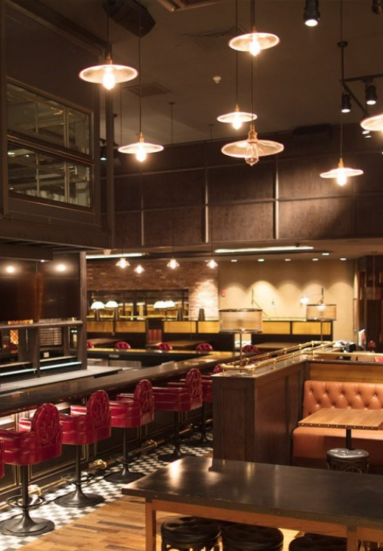 A dark wood restaurant with red barstools around a long bar