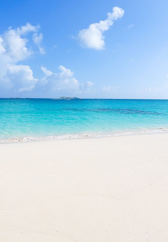Sandy beach with blue water and boat in the ocean