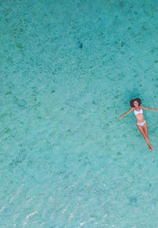 Aerial shot of woman laying on her back in the ocean