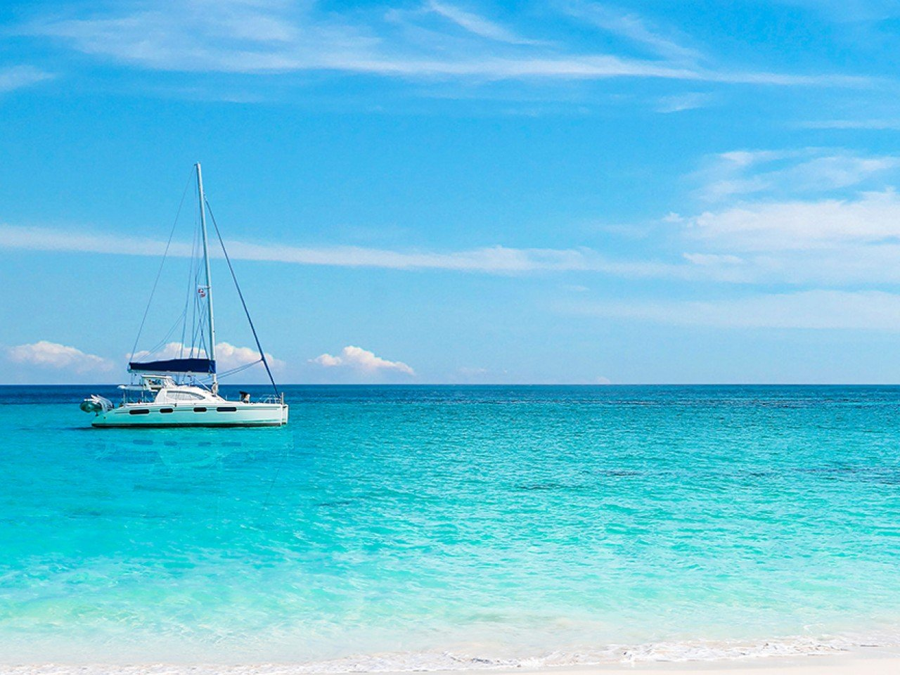 white yacht sits on clear blue water