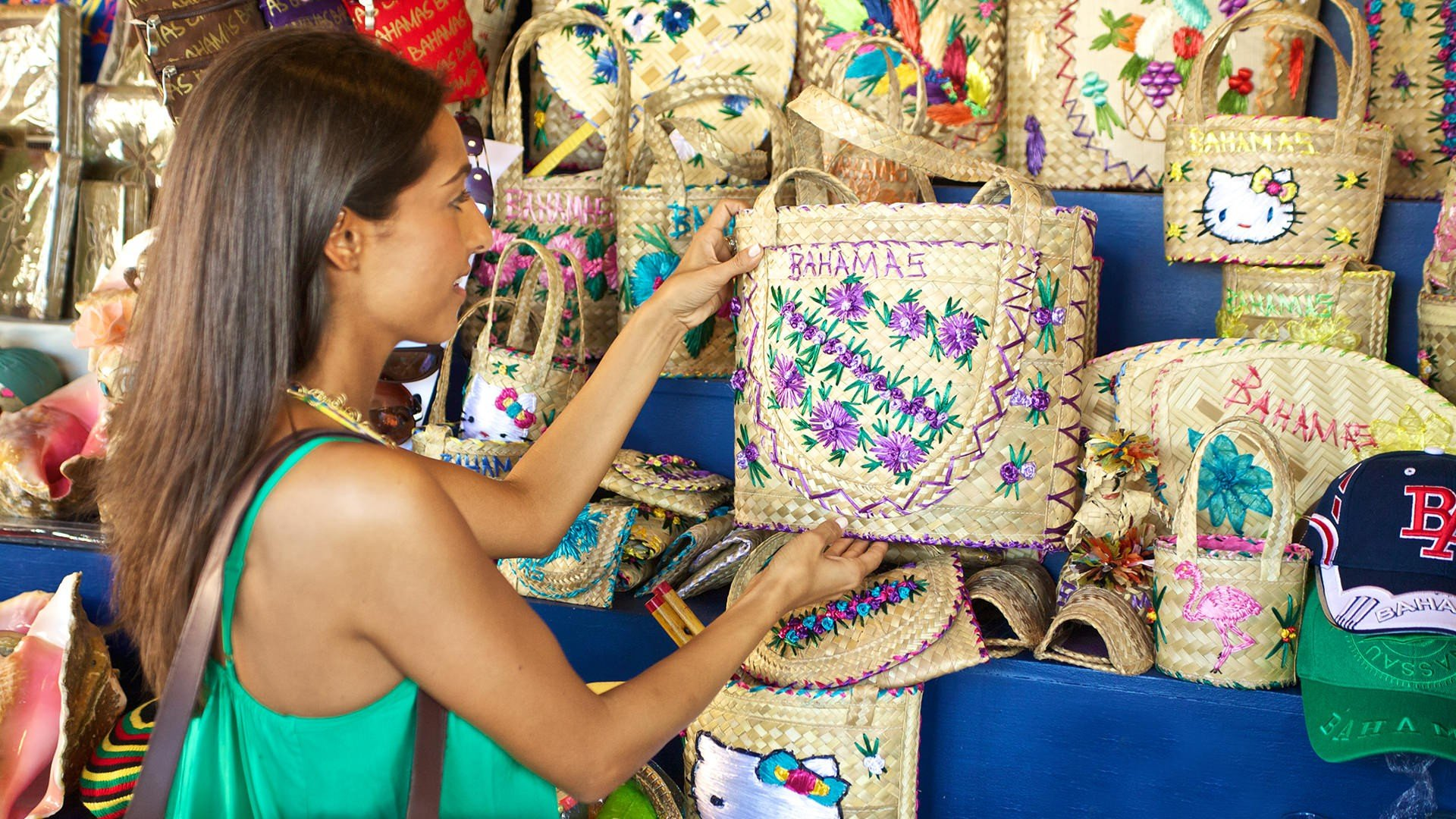 c405d372eb6 A woman looking at an intricately detailed bag at the Straw Market.